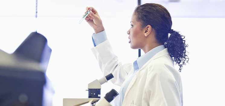 A doctor in a lab in front of a microscope holding up a test tube closely examining it