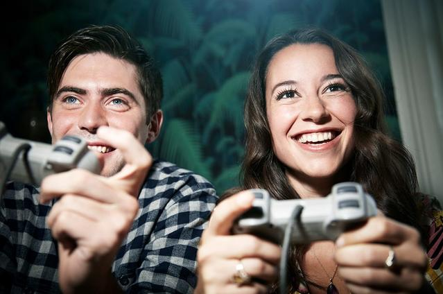 Two adults holding controllers playing video games